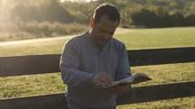 a man standing outdoors reading a Bible