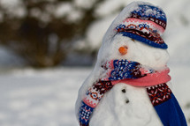 new snow on a snowman wearing a hat and scarf
