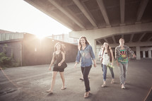 Teens walking  under an overpass.