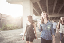 A group of young people walking under a bridge