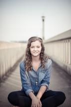 teen girl sitting on a sidewalk