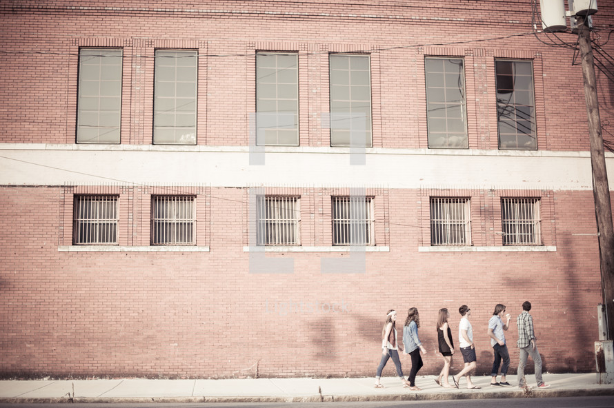 youth walking in a line on a sidewalk