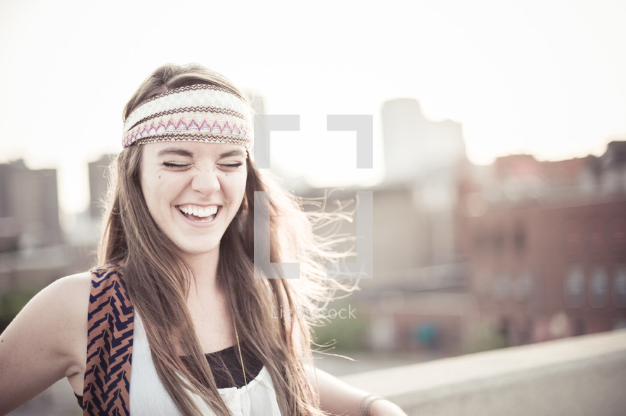A young woman laughing on the roof of a building