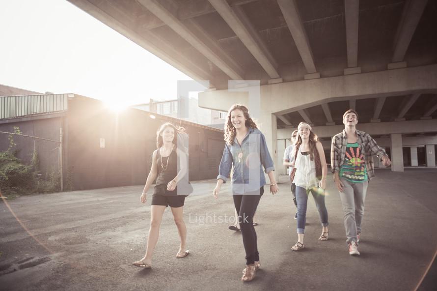 Teens walking  under an overpass.