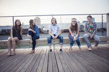 group of teen friends sitting on a bench on a boardwalk