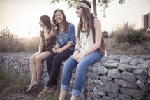 young women sitting on a stone wall together