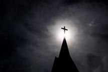 light shining on a cross on a steeple