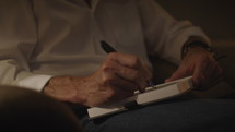a man writing in a journal