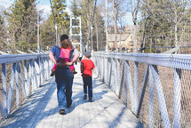 a father walking across a swinging bridge with his kids