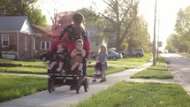 Mother and Father pushing children in stroller around neighborhood.