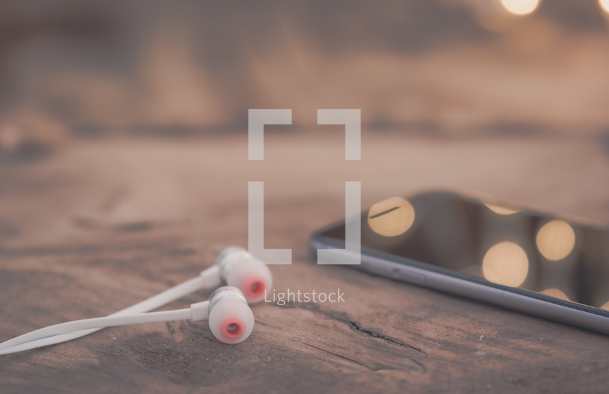 earbuds and cellphone on the pages of a bIble