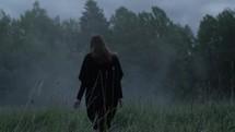 a woman walking through a foggy field