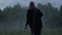 a woman walking through a foggy field