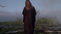 a woman in a flowing cloak walking through a misty mountaintop landscape