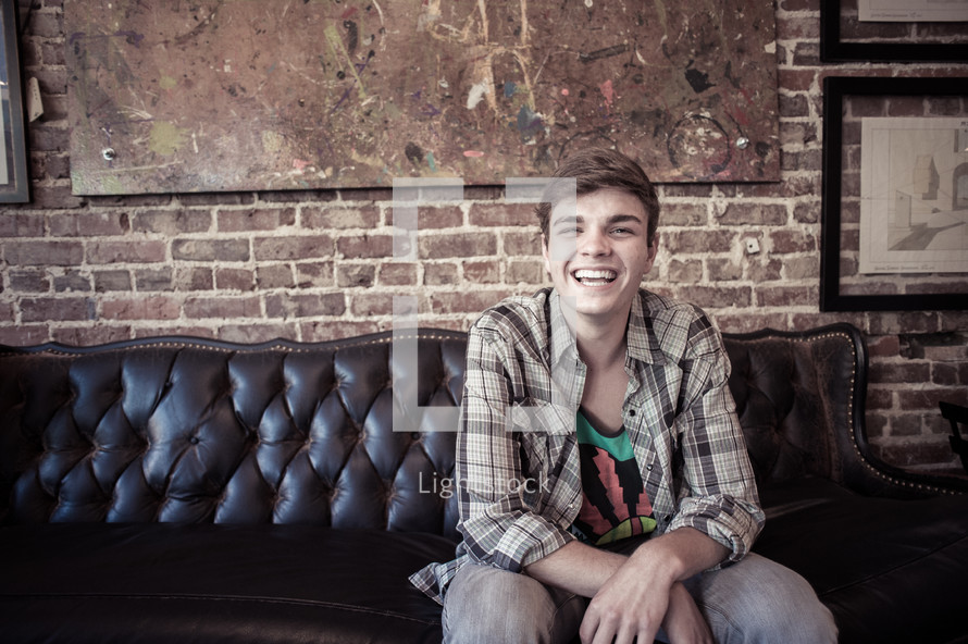 man sitting on a leather couch smiling