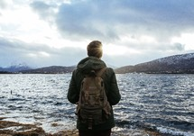 man with a backpack standing on a shore looking out at the water