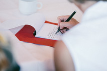 Woman writing a letter with pen and paper.