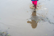 a toddler girl walking in a puddle