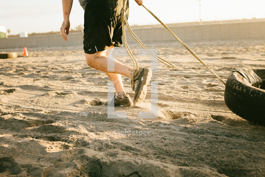 man dragging a tire in the sand