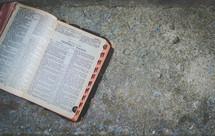 open Bible on a sidewalk