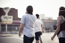 teens walking on a road together