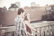 Teen couple on a roof balcony.