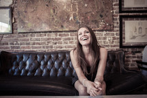 woman sitting on a leather couch smiling