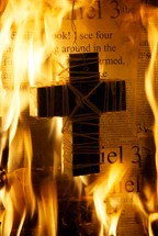 cross dangling over burning Bible