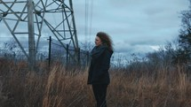 woman walking through a field and tall power lines