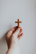 hand holding up a wooden cross