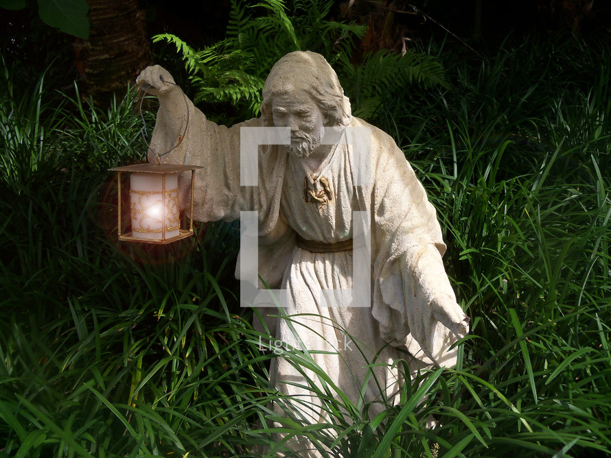 Statue of an Israelite holding a lantern to light his way through a thick path of grass and weeds as he travels by night.