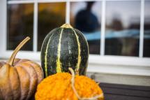 gourds and pumpkins near a window