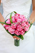 Bride holding bouquet of pink roses.