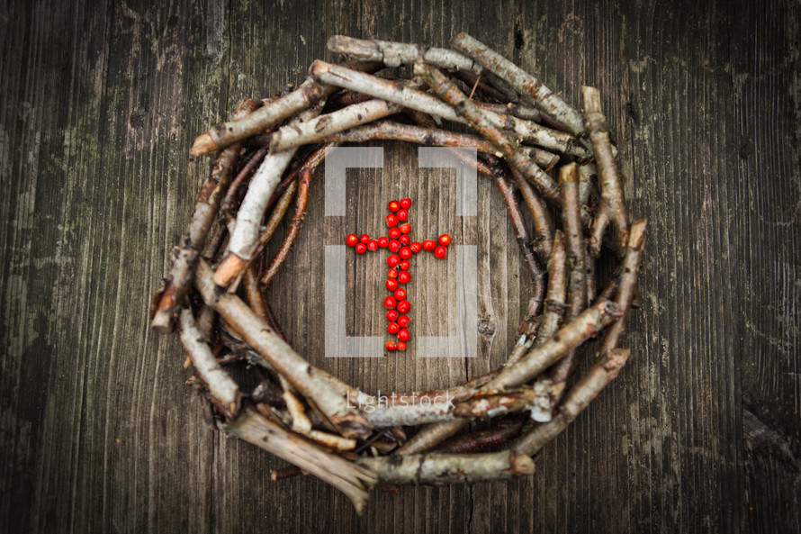 a wreath of sticks around a cross of red berries