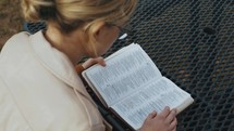 a woman reading a Bible outdoors
