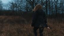 a woman walking through a field