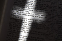 light glowing on the words of the pages of Bible in the shape of a cross