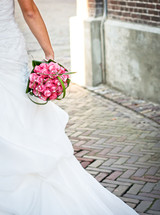 A bride holding a bridal bouquet on a brick walk.