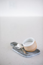 spoon of sugar and bowl on a cutting board in a kitchen