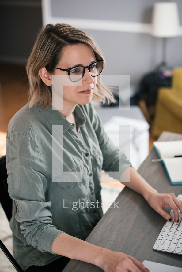 a woman sitting at a computer desk working