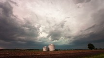 TImelapse of a thunderstorm approaching over rural farmland in the midwest.  A wall cloud forms and lightning strikes abound while a tractor scampers across the field.