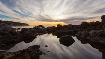 Timelapse of  sunset over the Pacific Ocean with tide pools reflecting the clouds among the rocks.
