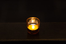 A glowing votive candle.