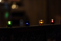 Candles glowing in colorful votives.
