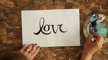 artist painting the word love