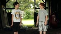 boys playing in mud in a barn