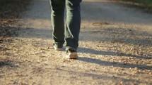 man walking down a dirt road