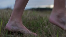 Feet  walking through a field.
