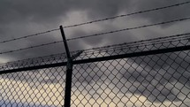 moving clouds and a barbed wire fence