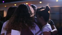 small groups hugging and praying at a youth conference